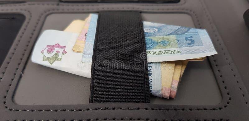Los billetes de banco de Hryvnia doblaron debajo del vendaje elástico en bolsillo negro imágenes de archivo libres de regalías