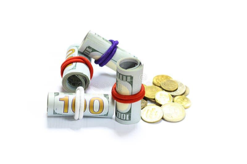 Los billetes de banco de las cuentas de dólar de EE. UU. rodaron y las monedas con el fondo blanco imagen de archivo libre de regalías
