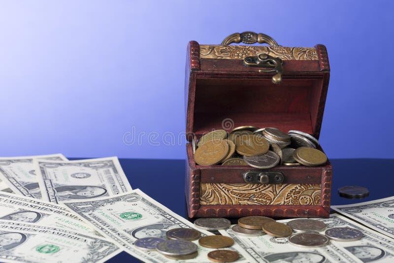 Los billetes de dólar americanos con el pecho llenaron de las monedas en fondo azul imagen de archivo