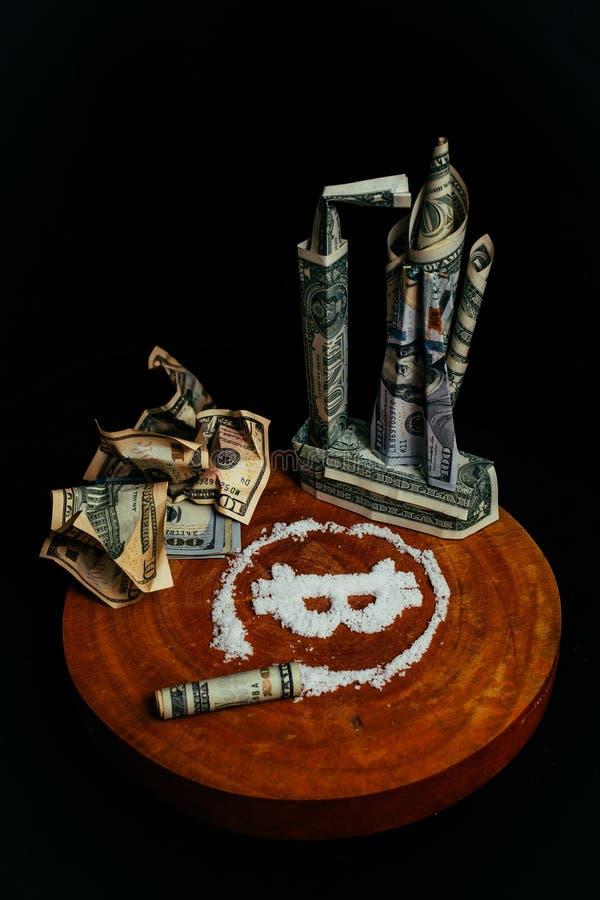 Los billetes de dólar se apilan bajo la forma de transbordador espacial Símbolo del bitcoin bajo la forma de drogas Billetes de b imagen de archivo