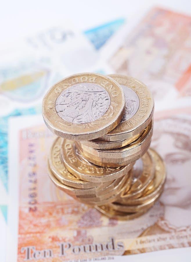 Los billetes y las monedas brit?nicos del dinero apilan fotos de archivo libres de regalías