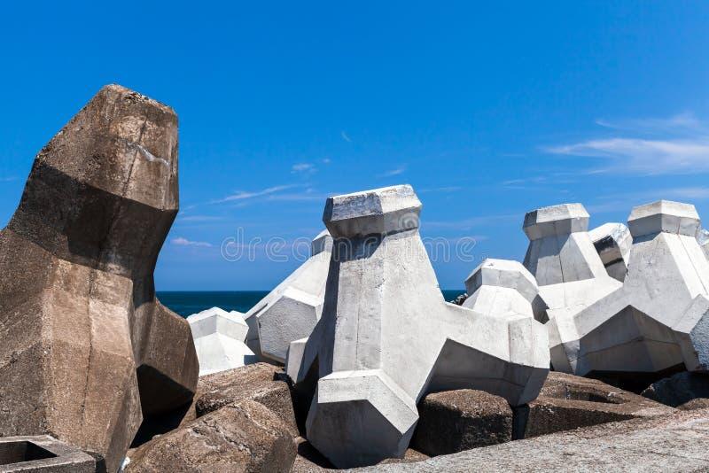 Los bloques concretos ásperos del rompeolas están debajo de cielo nublado fotografía de archivo libre de regalías