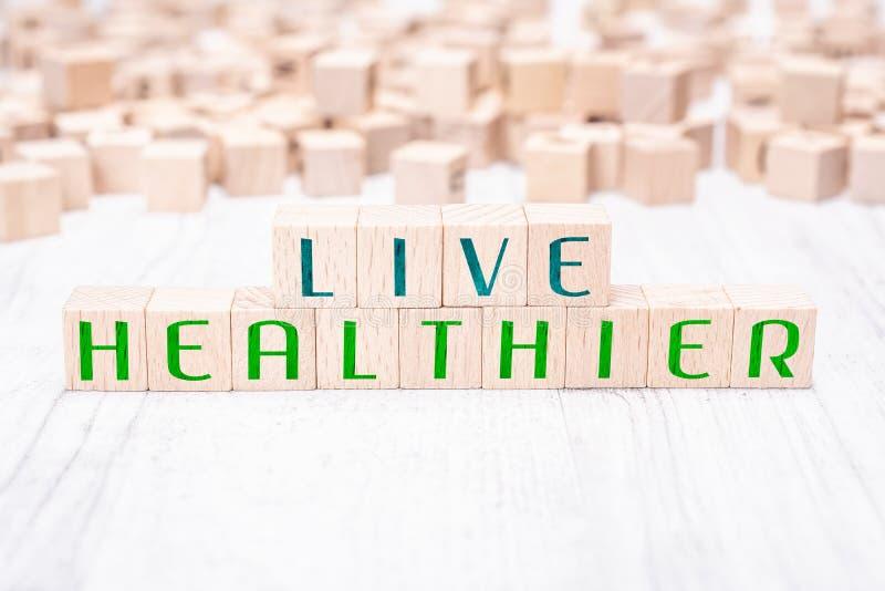 Los bloques de Live Healthier Formed By Wooden de las palabras en una tabla blanca imagen de archivo