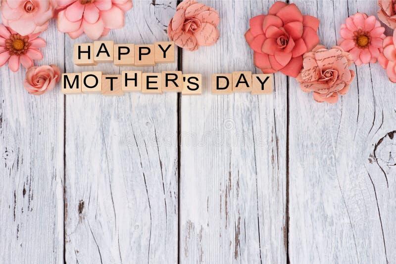 Los bloques de madera felices del día de madres con la flor rematan la frontera en la madera blanca imágenes de archivo libres de regalías