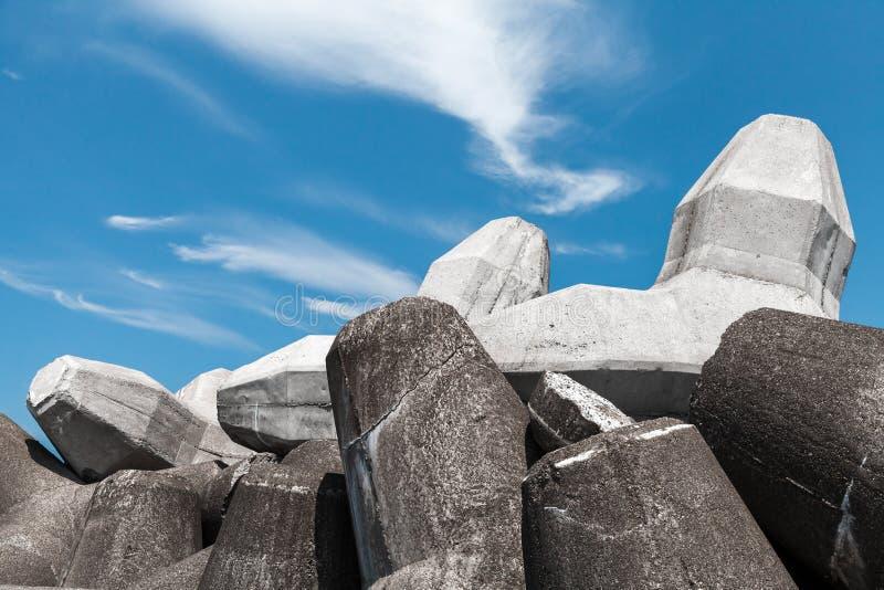 Los bloques del rompeolas hechos del hormigón están debajo de cielo nublado foto de archivo libre de regalías