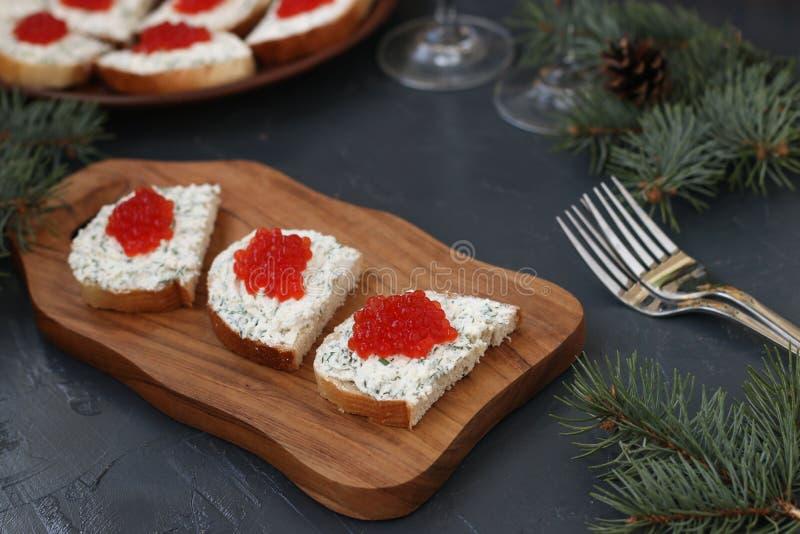 Los bocadillos con el caviar rojo están situados en un tablero de madera imágenes de archivo libres de regalías