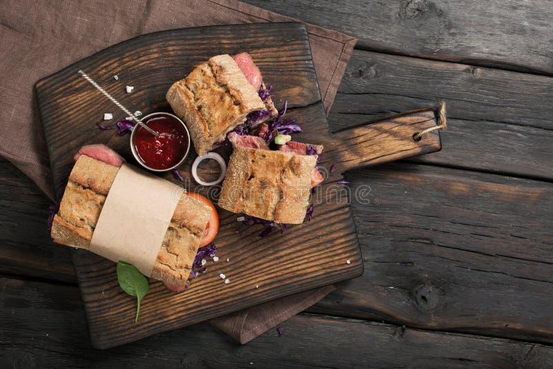 Los bocadillos con la carne asan a la parrilla en el viejo tablero marrón de la cocina imágenes de archivo libres de regalías