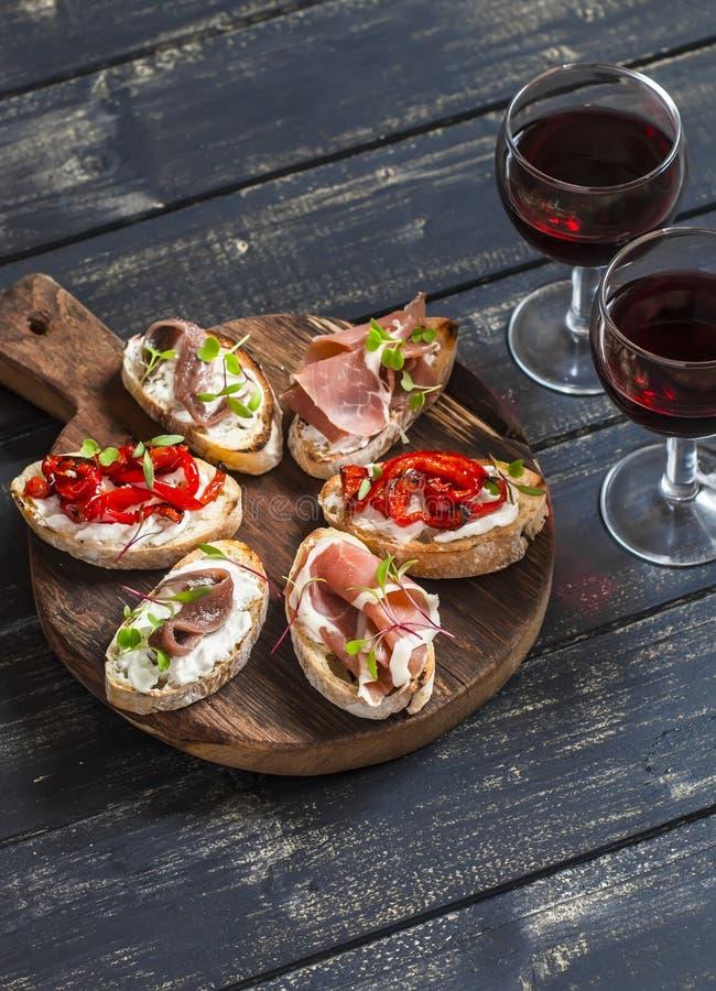 Los bocadillos con queso de cabra, anchoas, asaron las pimientas, el jamón y dos vidrios de vino rojo en un tablero rústico de ma fotografía de archivo