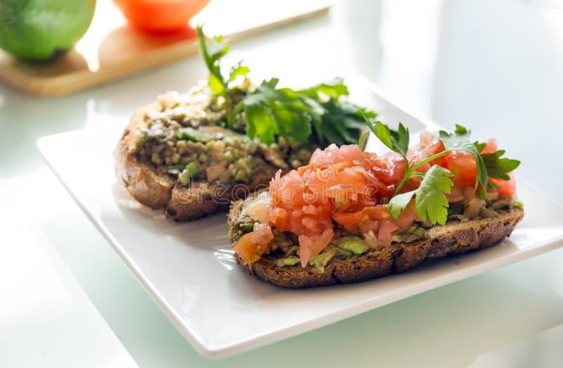 Los bocadillos, pan, aguacate, tomate con una puntilla del perejil, curan imagen de archivo