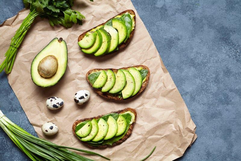 Los bocadillos tuestan con el aguacate, el guacamole y la espinaca en el pergamino en un fondo concreto Desayuno o almuerzo sano fotos de archivo libres de regalías