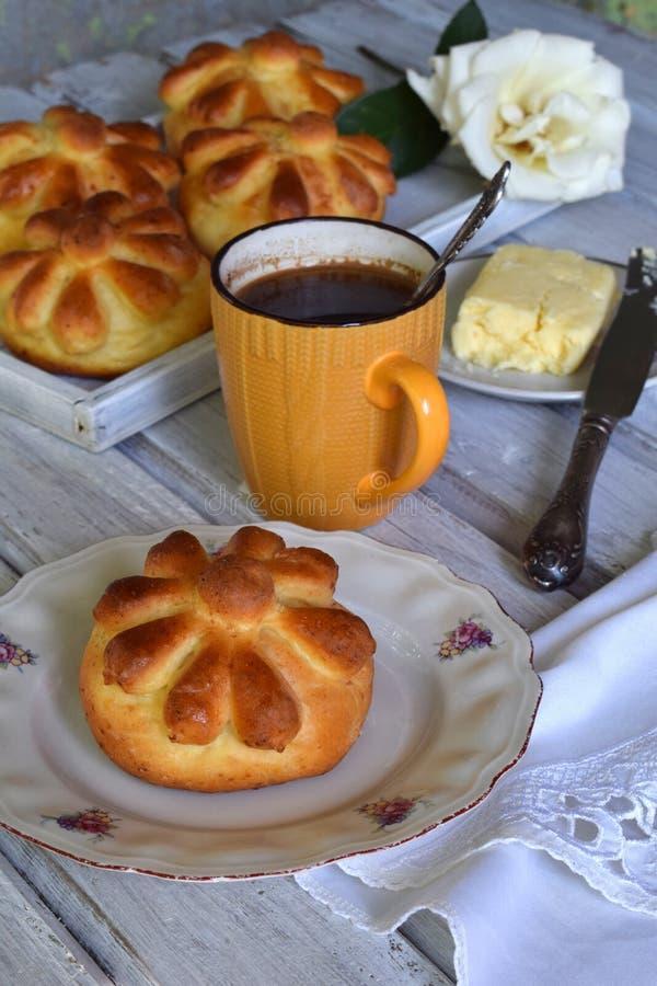 Los bollos de la cena del suero en forma de la flor sirvieron con el coffe de la mantequilla, del cuchillo y de la taza en fondo  fotos de archivo