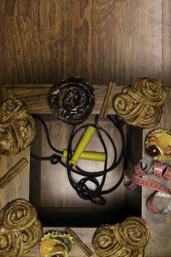 los bollos dulces del cinamon y del chocolate con cinta métrica, la comida malsana y la dieta miden el tiempo de concepto Fondo d imagenes de archivo