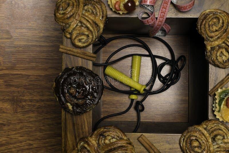 los bollos dulces del cinamon y del chocolate con cinta métrica, la comida malsana y la dieta miden el tiempo de concepto Fondo d fotos de archivo libres de regalías