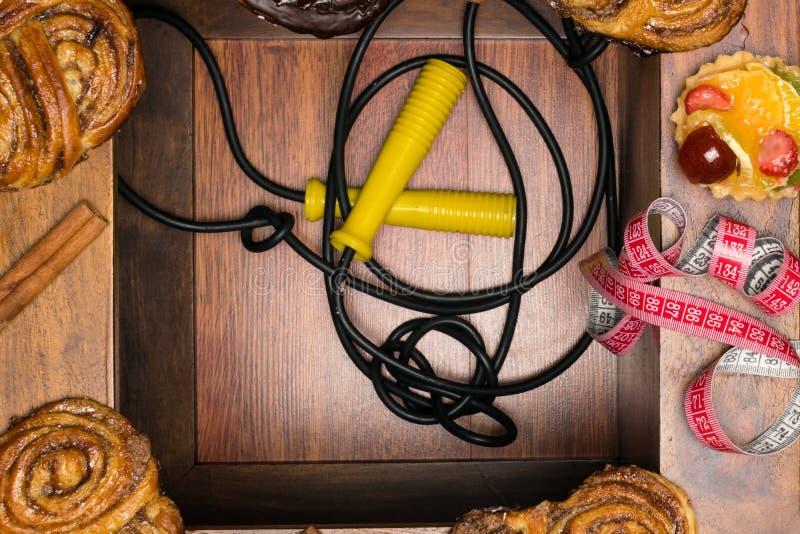los bollos dulces del cinamon y del chocolate con cinta métrica, la comida malsana y la dieta miden el tiempo de concepto Fondo d foto de archivo libre de regalías