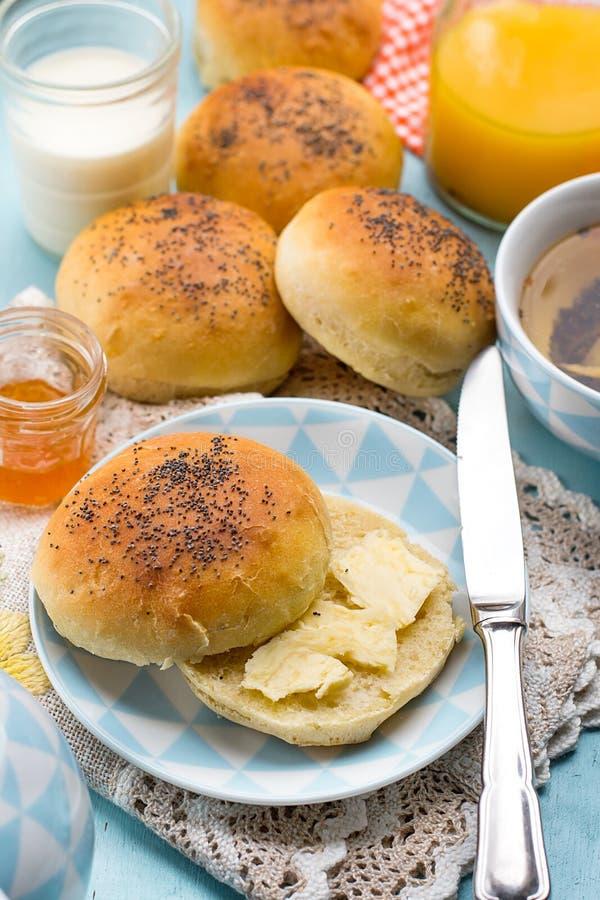 Los bollos ruedan con las semillas de amapola con la mantequilla para el desayuno fotografía de archivo