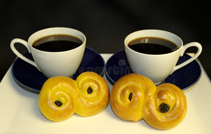 Los bollos tradicionales del azafrán con las tazas de café, tradición en Suecia en Lucía y la Navidad, en languag sueco llamaron foto de archivo
