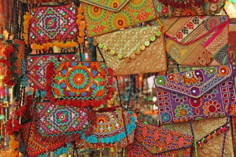 Los bolsos coloreados nacionales brillantes son productos cosméticos del bordado hecho a mano vendidos en el mercado en la India  fotografía de archivo