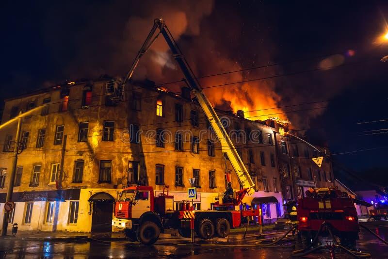 Los bomberos con la manguera de bomberos y los coches de bomberos o los camiones están luchando el fuego en el edificio residenci imagenes de archivo