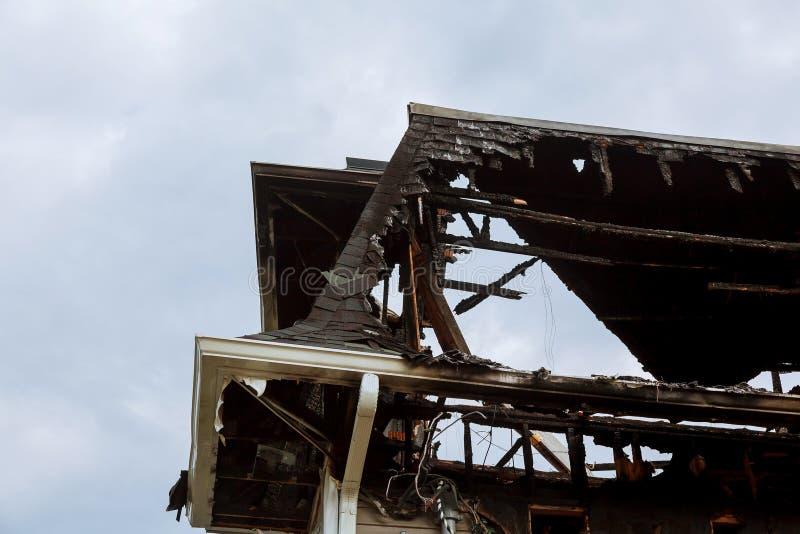 Los bomberos de los salvadores extinguen un fuego en el tejado El edificio después del fuego foto de archivo
