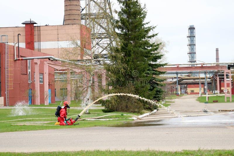 Los bomberos profesionales en trajes resistentes al fuego anaranjados en los cascos blancos con las caretas antigás están proband imagenes de archivo