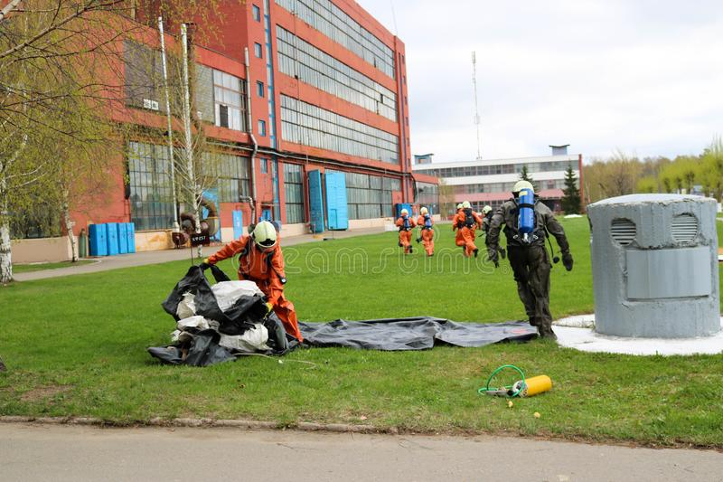 Los bomberos profesionales, los salvadores en trajes incombustibles protectores, los cascos y las caretas antigás huyen de gente  foto de archivo