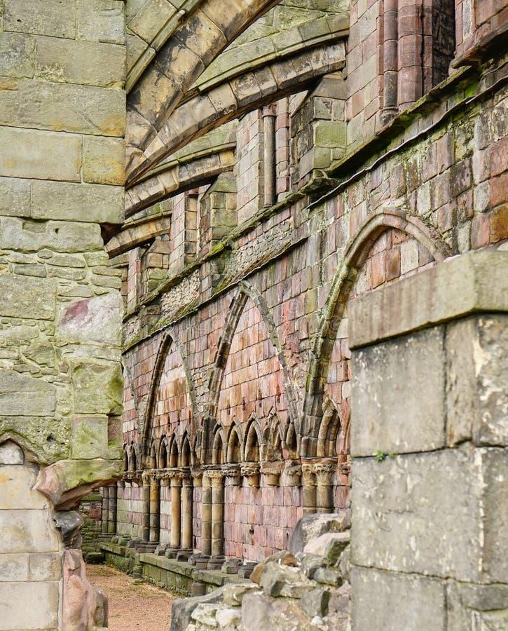 Los botareles apoyan una pared de piedra medieval hermosa de una ruina de la iglesia fotos de archivo