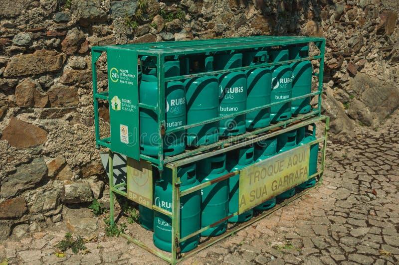 Los botes del gas del butano alistan para ser vendidos dentro de jaula de hierro imagen de archivo