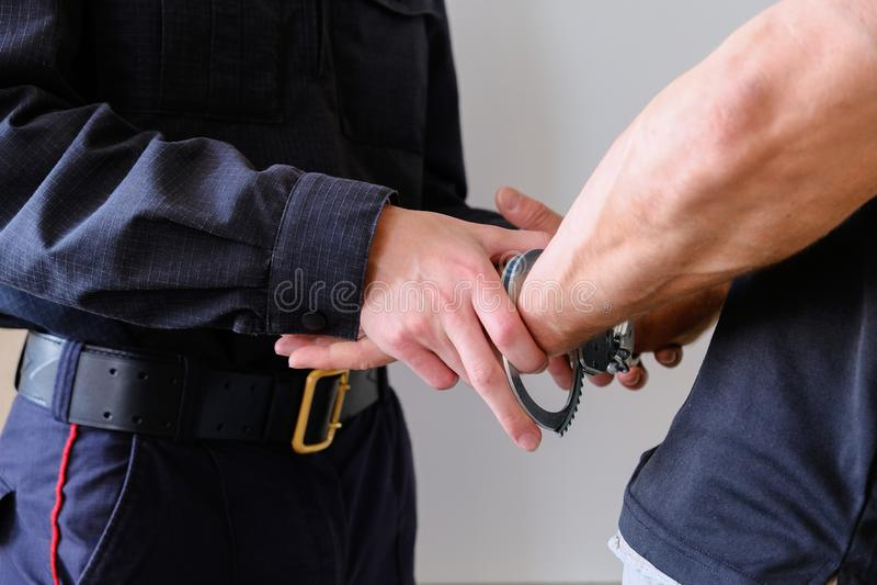 Los botones CAPTURAN las esposas un criminal arrestado El hombre en la comisar?a de polic?a Esposas en las mu?ecas del hombre det imagen de archivo
