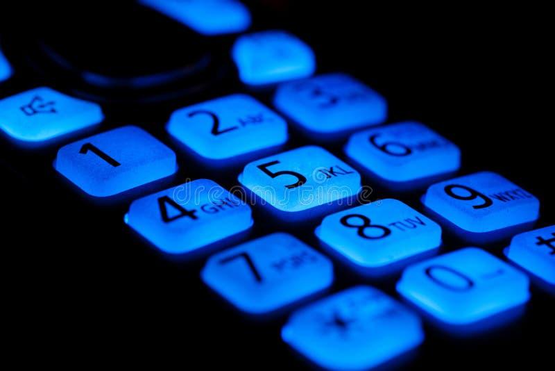 Los botones del teléfono se encienden para arriba en la macro de la noche fotografía de archivo