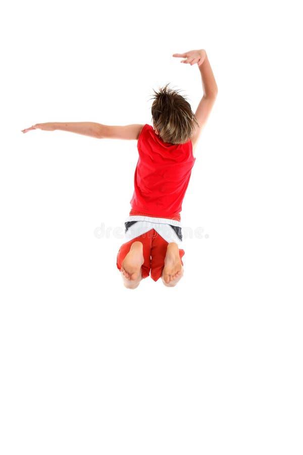 Los brazos de salto del muchacho en grande actitud. foto de archivo
