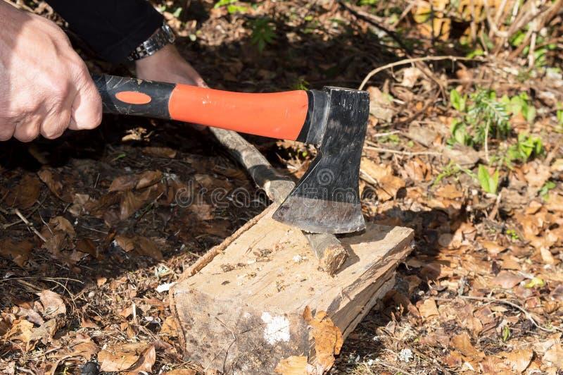 Los brazos del hombre del primer cortaron el palillo de madera con un hacha foto de archivo libre de regalías