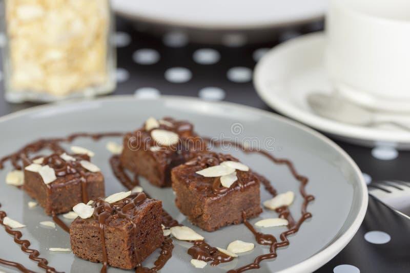 Los brownie del chocolate remataron con las rebanadas de la salsa y de la almendra imagen de archivo