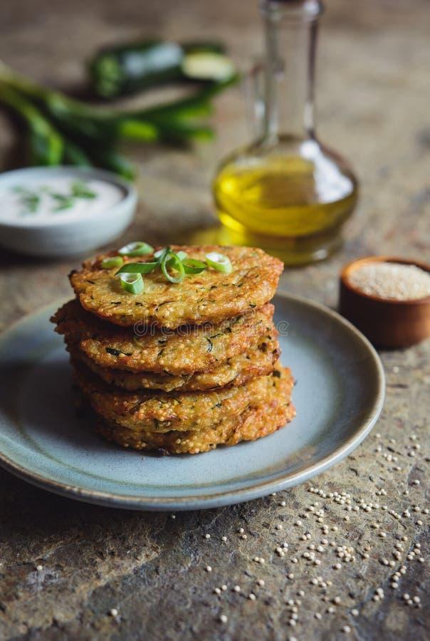 Los buñuelos de la quinoa con el calabacín, el ajo y la cebolla verde sirvieron con la inmersión del yogur fotografía de archivo