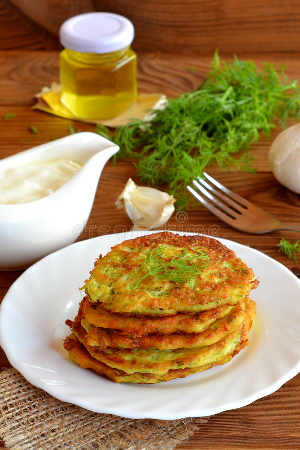 Los buñuelos vegetales cocinaron con el calabacín, el ajo y el eneldo Una pila de buñuelos del calabacín en una placa fotos de archivo