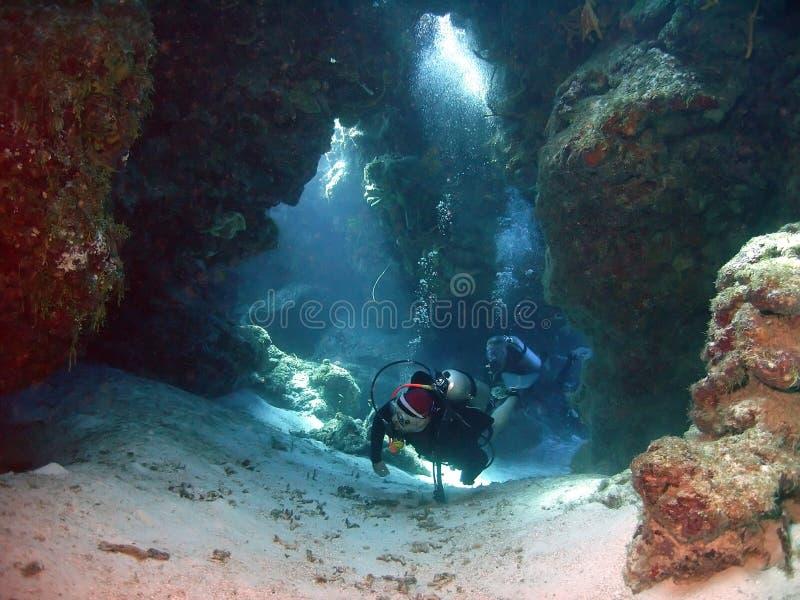 Los Buceadores De SCUBA Nadan Por Túneles De Coral fotografía de archivo
