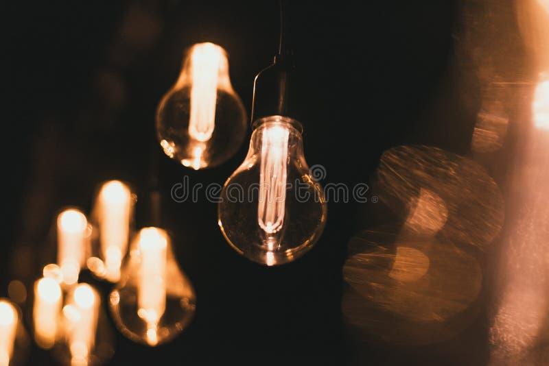 Los bulbos incandescentes retros amarillos cuelgan por la tarde en un partido Bombillas que cuelgan en un puente de madera en la  fotos de archivo