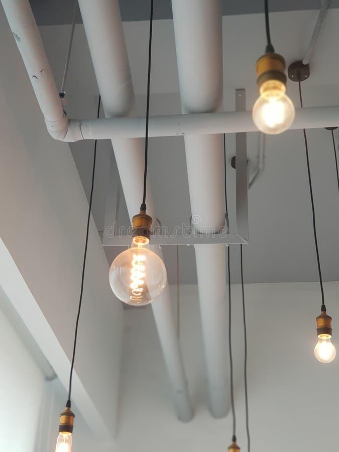 Los bulbos que flotan en el cielo de su oficina con el fondo instalan tubos foto de archivo libre de regalías