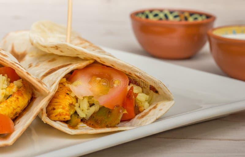 Los burritos mexicanos llenaron del pollo, de pimientas, de arroz y del tomate imagenes de archivo