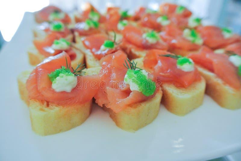 Los cócteles, aperitivos, salmón ahumado en el baguette adornan con c fotografía de archivo