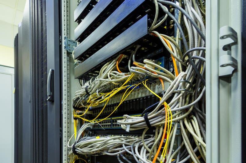 Los cables de fribra óptica conectaron con los puertos y Ethernet de la red de UTP fotos de archivo