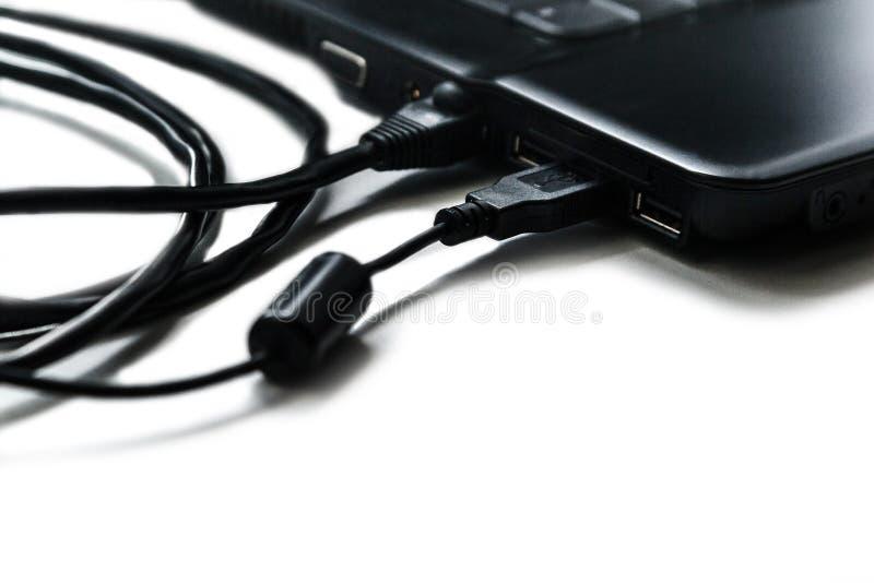 Los cables están conectados con el ordenador portátil fotos de archivo