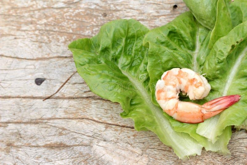 Los camarones con verde de las verduras se van en el fondo de madera imagenes de archivo