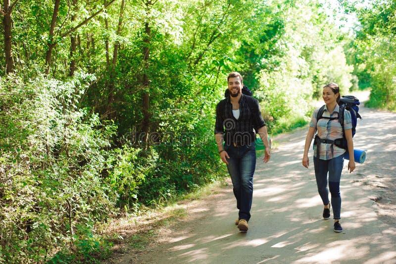 Los caminantes jovenes de los pares en bosque se divierten el hombre y a la mujer con las mochilas en el camino en naturaleza foto de archivo