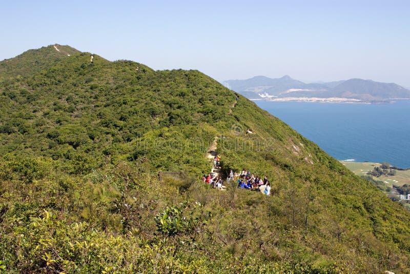 Los caminantes que atraviesan el pico del ` s del dragón se arrastran en Hong Kong, pasando por alto el océano imagenes de archivo