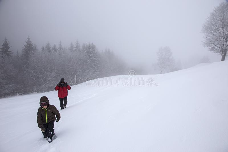 Los caminantes van para arriba en cuesta de la nieve en invierno Turistas que emigran en montañas del invierno en niebla fotos de archivo