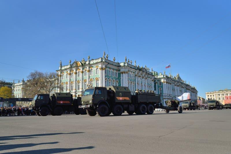 Los camiones de la artillería de división con los armas en el palacio ajustan durante foto de archivo