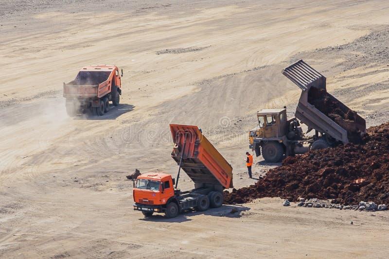 Los camiones en la parte inferior del hoyo descargan la tierra imagenes de archivo
