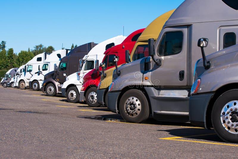 Los camiones grandes de los aparejos semi de diferente hacen que y los modelos se colocan en fila imagenes de archivo
