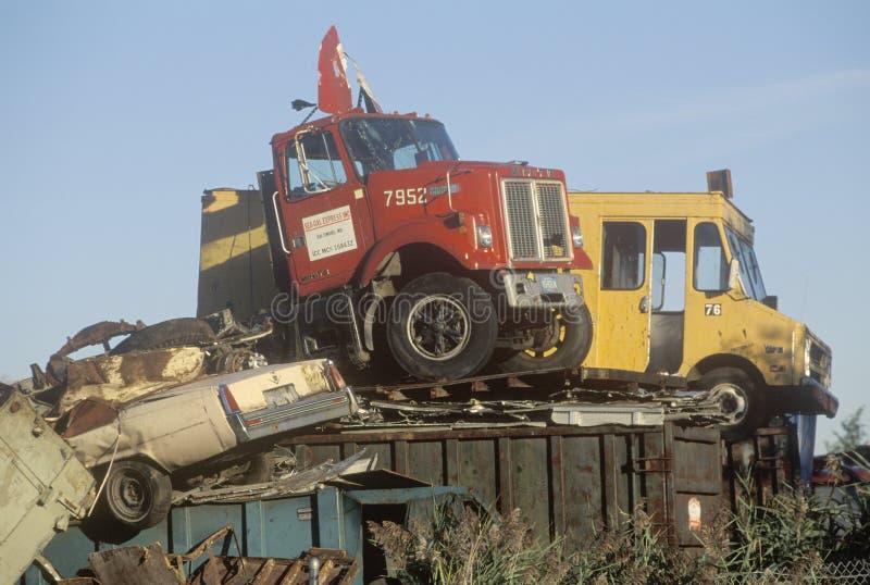 Los camiones viejos y los coches que se sientan encima de un pedazo apilan en un desguace en New Jersey imagen de archivo