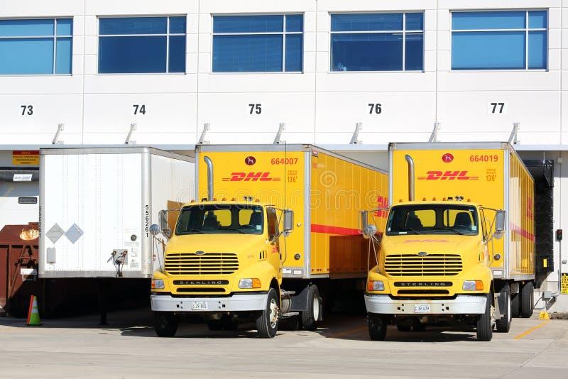Los camiones y los remolques de DHL parquearon en un almacén fotografía de archivo